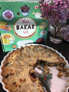 Bild på bokens omslag med olika kakor, en vas med syren, en paj som det tagits en bit av