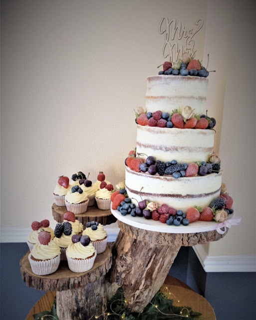 semi naked three tier wedding cake with fresh fruit and cupcakes