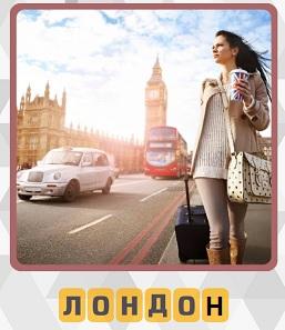 на улицах Лондона идет девушка с чемоданом и двигается транспорт