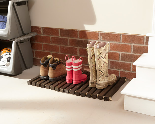dark stain wooden door mat holding shoes and boots