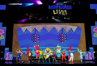 costumed characters appear on stage in a performance of Baby Shark Live