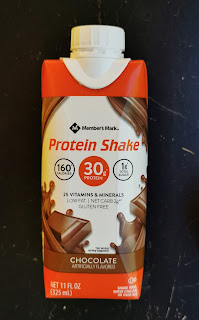 A carton of Members Mark Chocolate Protein Shake sitting against a black backdrop