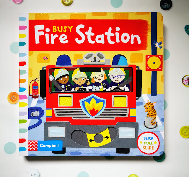 Image of front cover of Busy Fire Station by Campbell Books and Jo Byatt. The cover shows an image of a bold colourful fire engine and four fire fighters of different genders and different ethnicities. There is also an interactive element that goes side to side and makes it appear that the engine lights are flashing. There is a logo that indicates there are elements to push, pull and slide throughout the book.