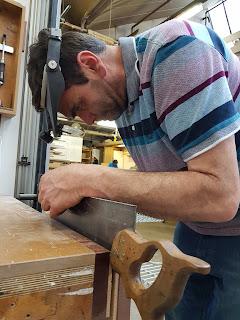 Man wearing an Optivisor and sharpening a saw.