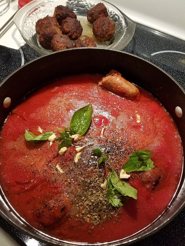 Italian tomato sauce in a big pot filled with crushed tomatoes, topped with basil, fresh garlic cloves, fresh oregano, meatballs and sausage is in the pot simmering to make this traditional Sunday sauce