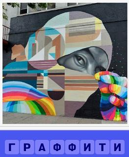 на стене дома нарисовано граффити, голова девушка закрытая платком