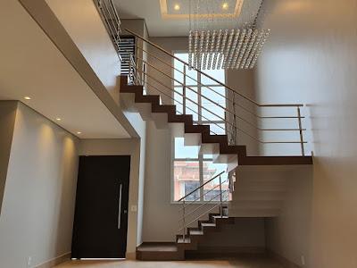 O interior deste sobrado é marcado pelo pé-direito duplo nas salas de estar e jantar, cuja escada de perfil aparente conduz ao mezanino que dá acesso às suítes.