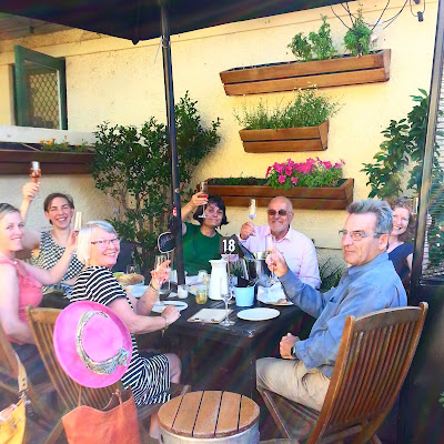 Group of people around an outdoor table, toasting the photographer with glasses of sparking wine.