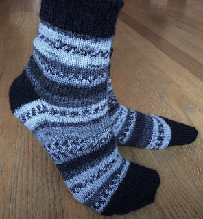 Hand-knitted wool socks in DROPS Fabel Salt and Pepper and Black with asymmetrical wedge toes and traditional heel flap