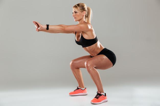 mulher fitness fazendo agachamento em casa