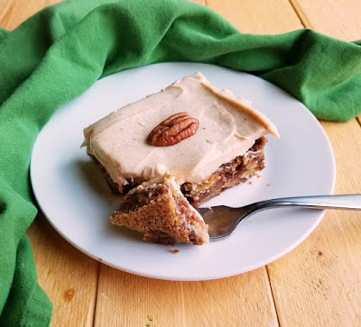 piece of dense german apple cake with cinnamon cream cheese frosting ready to eat