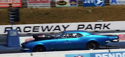 Metallic blue 1967 Camaro with blower scoop wheelie bar and parachute launches down the track