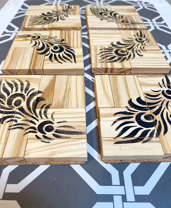 rows of coasters with feathers stenciled on top