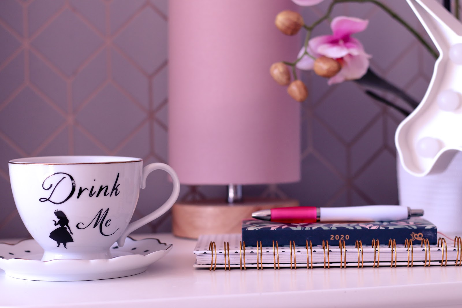 Close up photo of a 2020 diary and a white tea cup on top on a white side table with a pink lamp and faux pink orchid in the background blurred.
