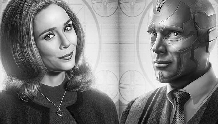 A foto em preto e branco mulher sorrindo com a cabeça inclinada. Ela é branca e o cabelo dela é ondulado e na altura do ombro ao lado dela tem um robô de pele feita de metal ele usa um terno e um suéter.