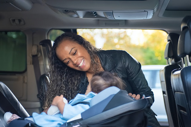 A woman placing her baby in a car seat in a car