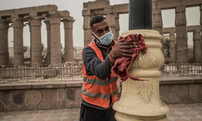 "A worker cleaning a light post in Luxor ""AFP"""
