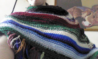 A shawl wrapped around the shoulders and neck of a person. The shawl is a number of various colours and stripes of various thickness, and the bottom edge of the shawl is fringed.