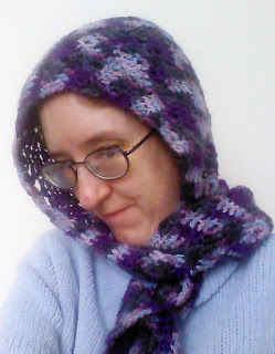 A woman wearing a hood with a scarf. The hood is done in worsted-weight crochet in a chevron pattern. The yarn is variegated yarn that runs between purple, black, and grey.