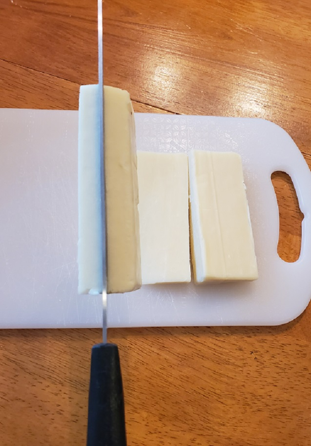 This is sticks of cheese cut up on a white cutting board. The block of sharp provolone cheese is being cut with a sharp Wilkinson knife