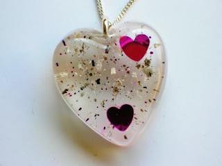 Heart shaped memorial pendant containing ashes and pink hearts