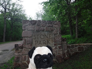 "a large stone wall has a square pillar that has the words ""Stone Park"" carved into it"