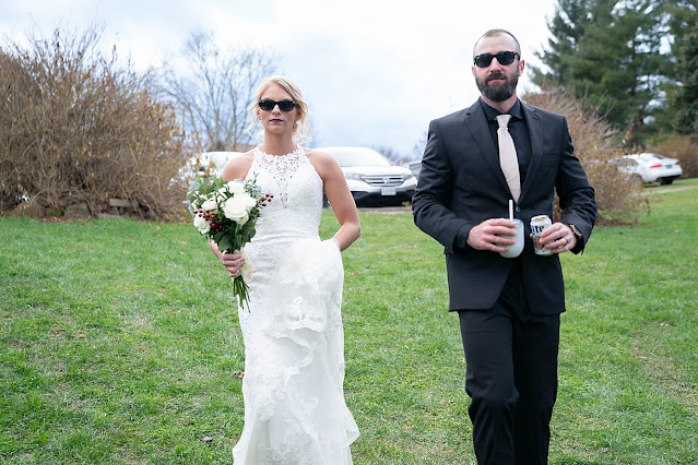 Bride and Groom walking together with bouquet and bud lights in hand and sunglasses on Magnolia Farm Asheville Wedding Photography captured by Houghton Photography