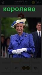 На фотографии стоит королева в синем платье и синей шляпе