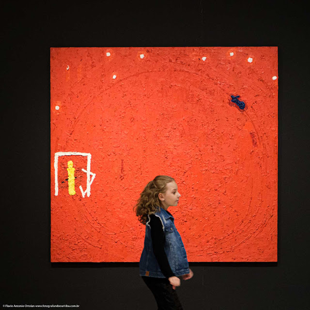 Menina em frente a pintura a óleo no museu