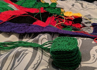 A stack of green crochet squares in the foreground, with the work in progress blanket in the background.