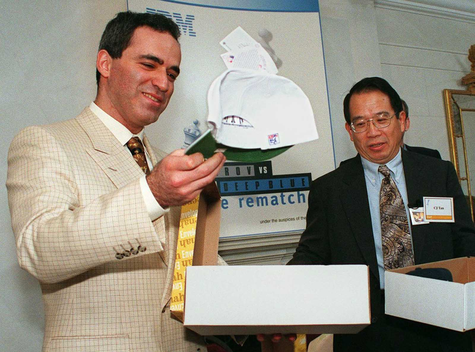 Kasparov lifts a white hat which signifies that he will have the first move in his rematch with Deep Blue.