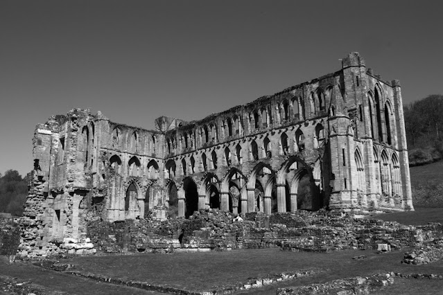 Monochrome photo of the main ruins from well back. The grass and smaller ruins are in the foreground.