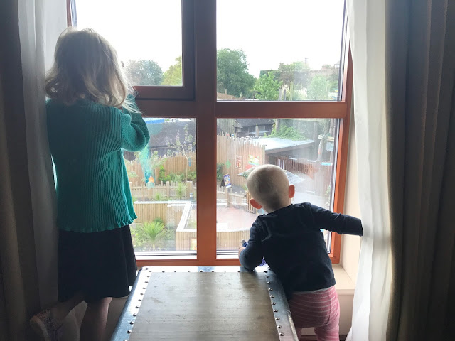 My 5 year old and 1 year old looking out the hotel room window ready to go on an adventure