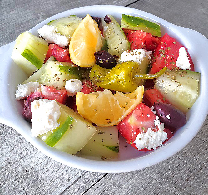 this is a greek salad with dressing and in a white bowl
