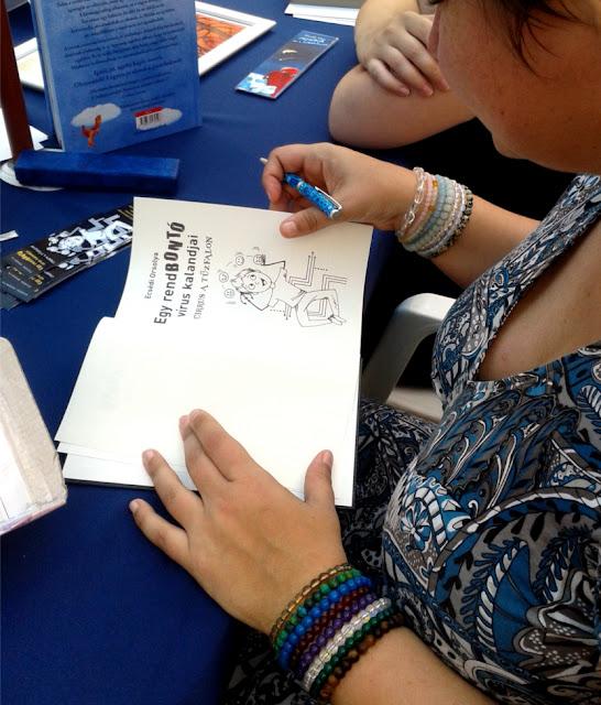 Budapest, Vörösmarty tér, 89. Ünnepi Könyvhét, 2018. június 10., Könyvmolyképző stand, Ecsédi Orsolya dedikálja Cirrus a tűzfalon című könyvét.