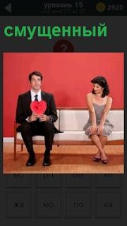 На диване смущенный мужчина отодвинулся от женщины на расстояние и в руках бумажное сердце