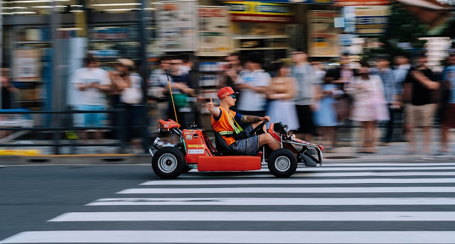 Man driving around in Akihabara streets with a rental Go-kart while giving a thumbs up to the camera and many locals and tourists watching him in the background