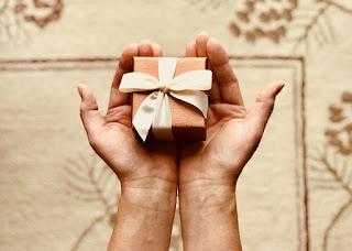 A person holds a small gift box in their outstretched hands. The gift box is a slightly metallic brown colour, with a cream-coloured bow around it.