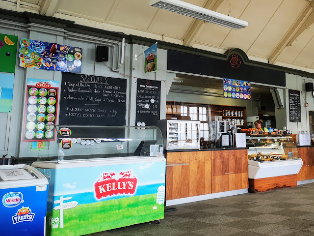 Image of the interior of the Rose Garden café in Sheffield's Graves Park. Image shows a nestle ice cream freezer, a Kelly's ice cream, the counter with a cake display and chalk boards along the walls listing the daily specials available in the café.