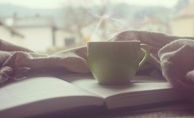 Steaming cup of coffee on top of open pile of books