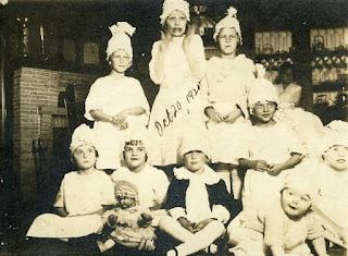 Group of children in white dresses wearing white, pointed hats. Seated in a living room with fireplace in background