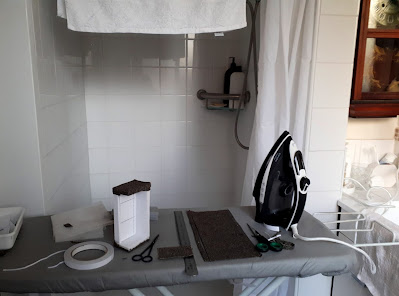 Ironing board set up in an ensuite, with a variety of craft supplies, an iron and a half-finished one twelfth scale modern miniature sofa on top of it.