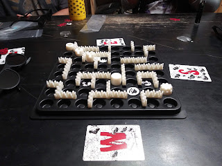 The board during a game in progress. Several barriers shaped like a row of trees are placed between two adjacent spaces to form a maze around the board. Several of the 'barrels' can be seen around the board. There are also rock tokens in a few places. Cards denoting the cardinal directions (north, south, east, and west) are placed around the board to help people remember which way is which.