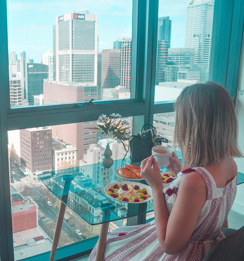 girl sitting at melbourne hotel window looking at beautiful city view of skyscrapers instagram fashion travel blogger