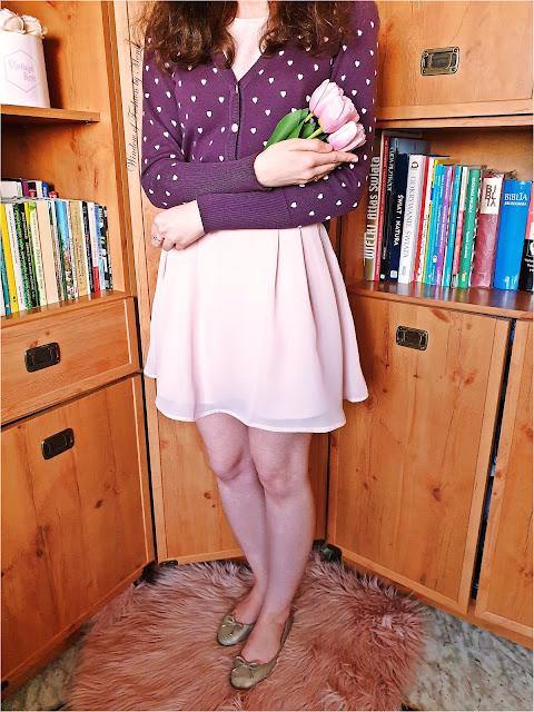 Fioletowy sweter w serduszka, jasnoróżowa sukienka, złote baleriny, złote pierścionki z serduszkami, złoty choker z kółeczkami, bukiet różowych tulipanów