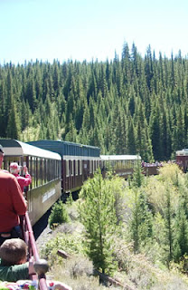 Passenger train ride on a big mountain curve on a sunny afternoon.  Passengers standing along the railing looking at the scenery and taking photos.