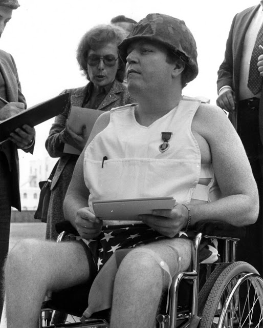 Hustler magazine publisher Larry Flynt, 1983, interviewed by the press, going to court in a wheelchair, wearing the US flag as a diaper, a soldier's helmet, and a purple heart pinned to a bulletproof vest. Court Complexities and Legal Fiction, A Moron In A Hurry marchmatron.com