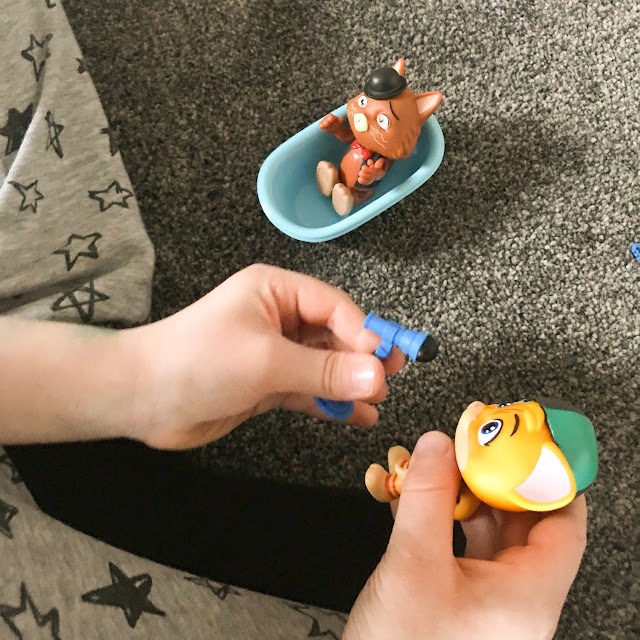 Close up of a child's hands holding and playing with the figures