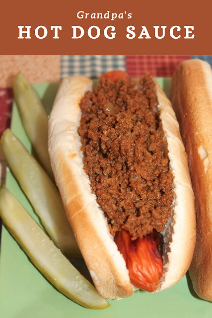 Close-up of finished hot dog topped with the hot dog sauce and pickles on the side.