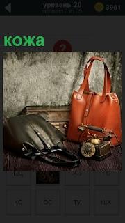 На столе лежат две сумки, сделанные из кожи и рядом старинный телефонный аппарат
